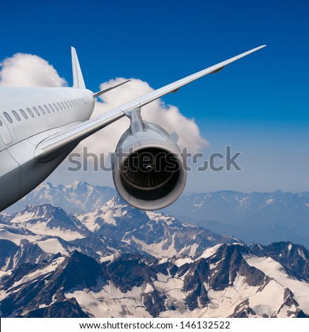 plane flying over the snow-capped mountains. airplane flying down. against the sky.  landing or crash of airplane - stock photo