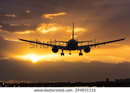 Plane flying towards the morning sun. - stock photo