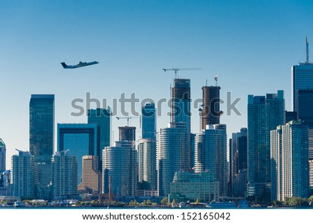 Plane flys over the city(Building signs are removed) - stock photo