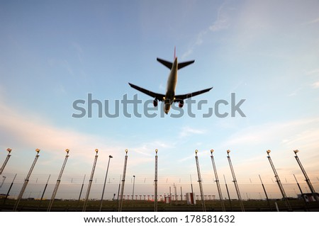 Plane is flying over landinglights. Note that the lights is in focus and the plane is in motion blure because of the speed. - stock photo