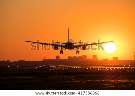 Plane is flying to the airport and landing at the runway at sunrise. Shot 2. - stock photo