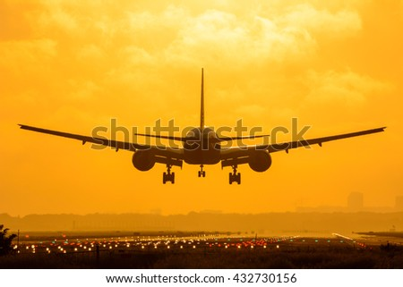 Plane is flying to the airport during a foggy sunrise.  - stock photo