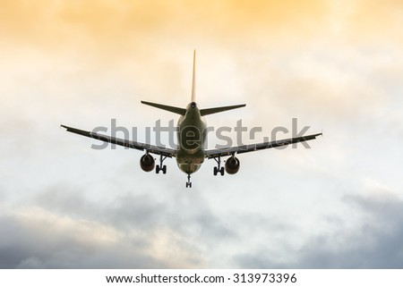 Plane is flying to the runway. Nice colorful cloudy background. - stock photo