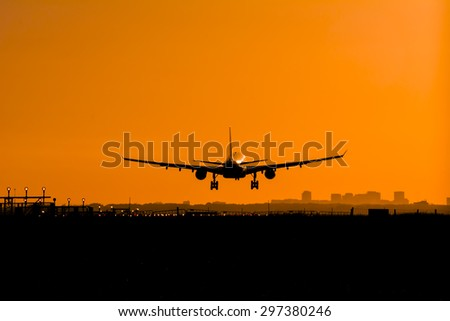 Plane is landing at dusk. - stock photo
