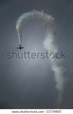 plane making U turn trail at sky with white smoke