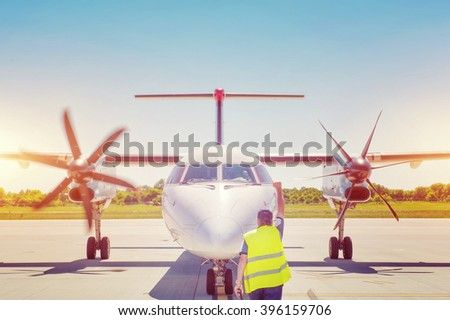 Plane on tarmac in the airport, guided by ground staff. Taxiing - stock photo