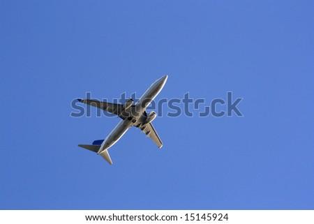 Plane on the blue sky. - stock photo
