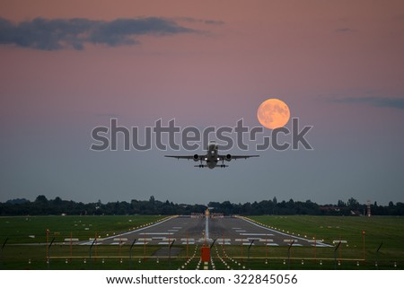 Plane take-off under the full moon - stock photo