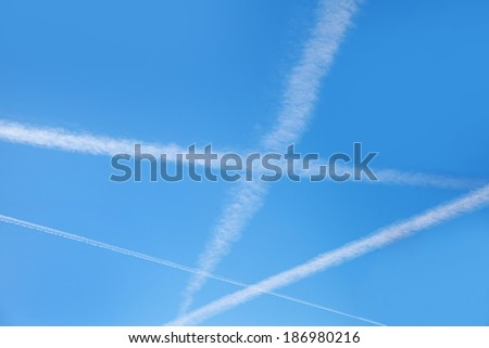 Plane trails in blue sky.