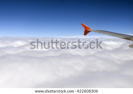 Plane trips between large white clouds. Fluffy white clouds view from above, in the sky. The wing of the plane cuts the atmosphere in the air. - stock photo