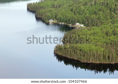 plane view of a fishing camp in a wild forest - stock photo