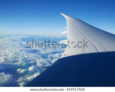 Plane wing and blue sky with beautiful clouds underneath and mountains in the background