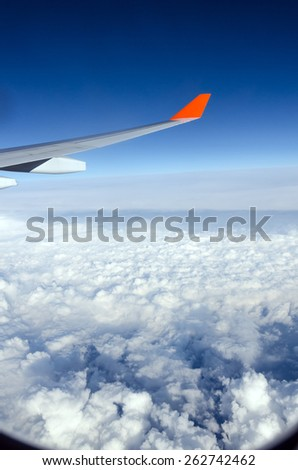 Plane wing, white clouds and blue sky - stock photo