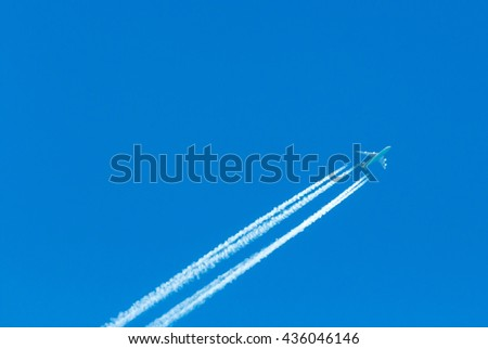 plane with contrails in the sky - stock photo