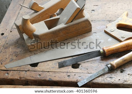 planes and two chisels and a saw on the Workbench with a wooden grip inside the craftsman joinery manufacturer - stock photo