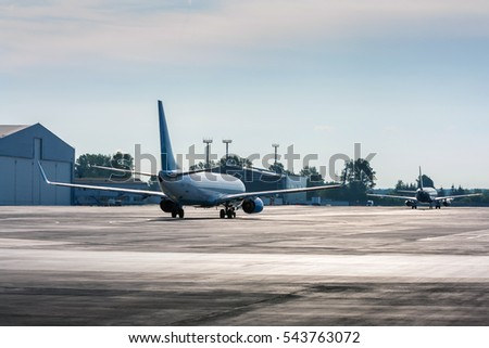 Planes taxiing one after another in backlit