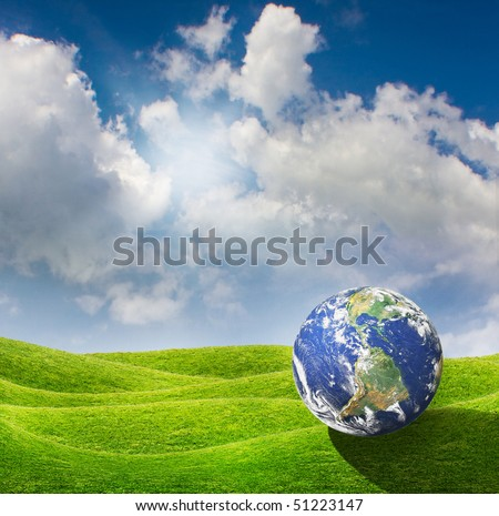 Planet Earth goes on a vacation at a beautiful green meadow. Beautiful spring sunny day with blue cloudy sky - stock photo