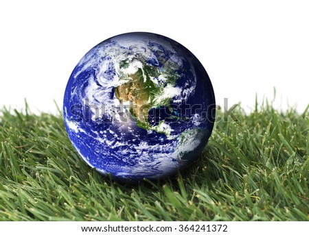Planet earth over green grass on a isolated background. The planet earth image provided by NASA. - stock photo