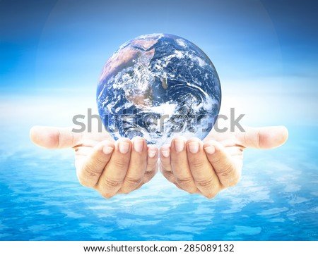 Planet in human hand over blurred beautiful blue sky and oceans background. Earth Day, World Environment Day and Creation from God, CSR, Love concept. Elements of this image furnished by NASA. - stock photo