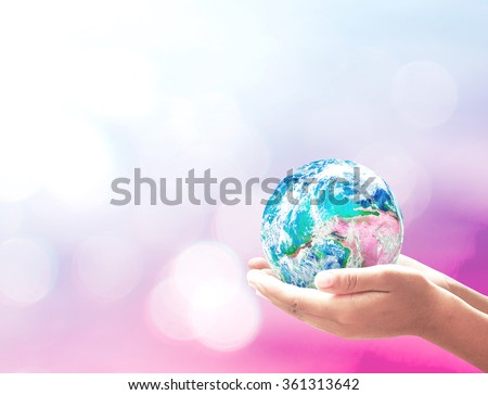 Planet in human hands on blurred nature background. Environment, World Autism Awareness Day, Earth Hour, CSR, Eco Friendly concept. Elements of this image furnished by NASA. - stock photo