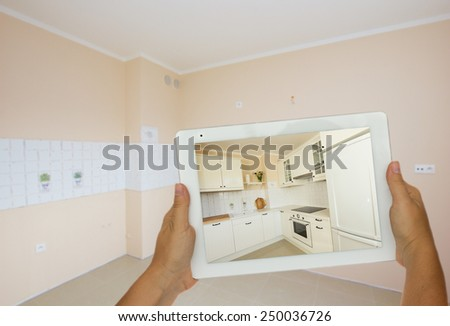 planing new kitchen furniture  on tablet in refurbished room - stock photo