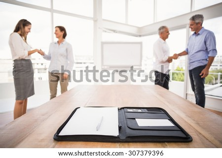 Planner in front of handshaking business people in the office - stock photo