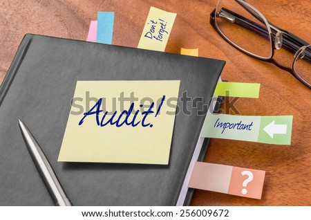 Planner with sticky note - Audit - stock photo