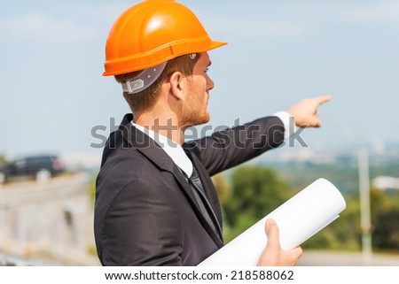 Planning a new construction. Rear view of confident young man in hardhat holding blueprint and pointing away while standing outdoors - stock photo