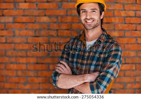 Planning a new construction. Smiling young man in hardhat keeping arms crossed and looking at camera while standing against brick wall - stock photo