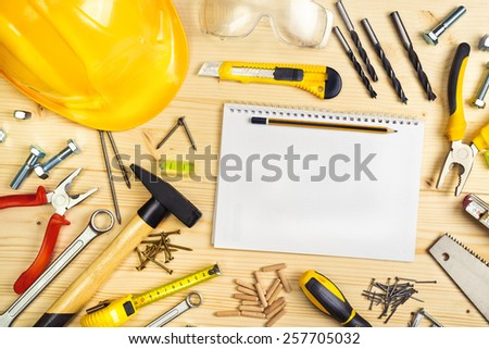 Planning a Project in Carpentry and Woodwork Industry, Notebook and Assorted Woodwork and Carpentry Tools on Pinewood Workshop Table, Top View. - stock photo