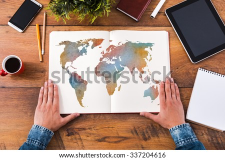 Planning his journey. Top view close-up image of man holding hands on his notebook with colorful map on it while sitting at the wooden desk - stock photo