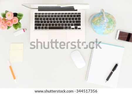 Planning next trip. Top view of working desk with laptop and other office equipment - stock photo