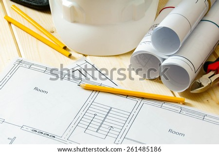 Planning of repair of the house. House construction. Drawings for building, helmet and others tools on wooden background.