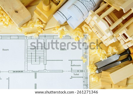 Planning of repair of the house. Woodworking. Drawings for building, small wooden house and working tools on wooden background. - stock photo