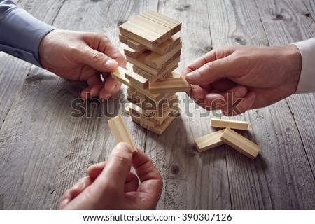 Planning, risk and team strategy in business, businessman gambling placing wooden block on a tower - stock photo