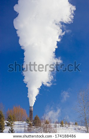 Plant pipe smoking behind the hill with trees against blue sky by winter - stock photo
