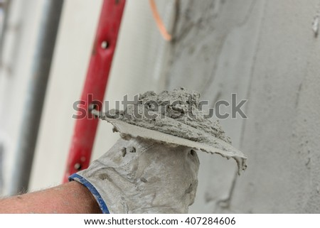 plaster a wall with ladle and concrete
