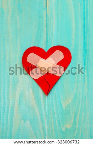 Plaster and paper broken heart on wooden background with copy-space