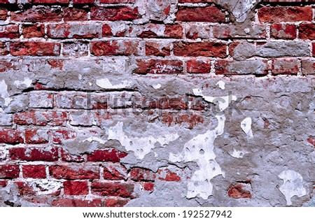 Plaster is showered from an old brick wall - stock photo