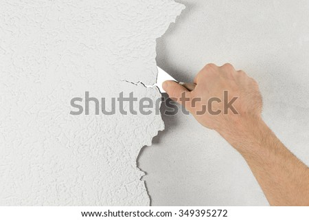 plaster removal with hand and spatula - stock photo