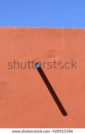 plaster wall with a protruding pipe and blue sky - stock photo
