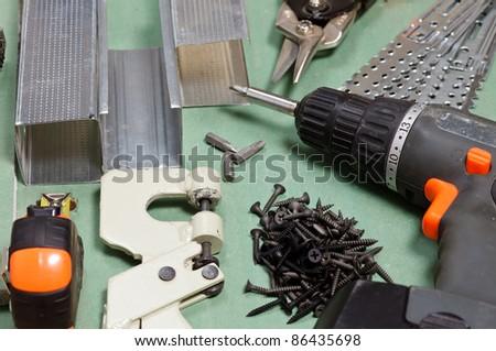 Plasterboard tools set with metal studs, screws, tape measure, screwgun and punch lock crimper - stock photo
