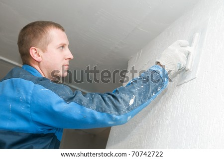 Plasterer at indoor renovation decoration with putty knife - stock photo