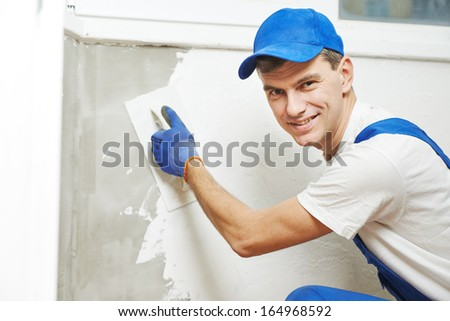 Plasterer at indoor wall renovation decoration with float and plaster - stock photo