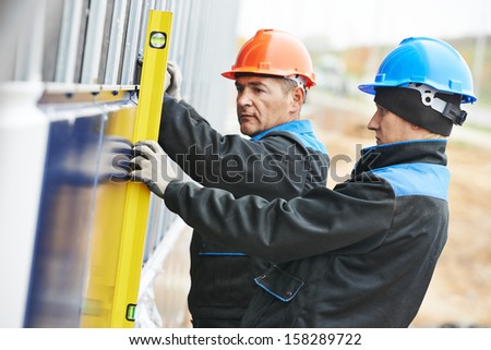 Plasterer builder worker with level examining granite stone marble facade works - stock photo