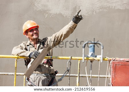 Plasterer Crafts Man Worker showing at distance during Construction Work for plastering multi storey building wall of bricks or concrete blocks - stock photo