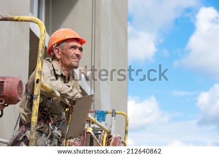 Plasterer man mountaineering builder worker looking at distance during construction works - stock photo