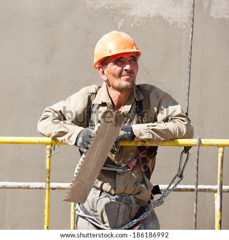 Plasterer man mountaineering worker looking at distance during construction works - stock photo