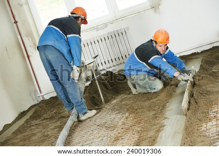 Plasterer workers at indoor concrete cement floor topping with float - stock photo