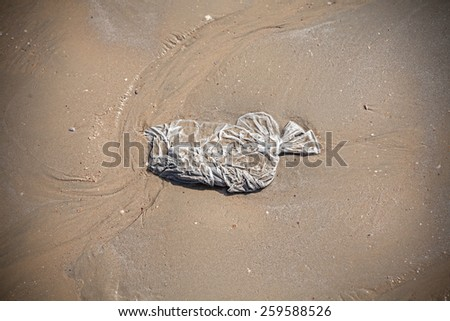 Plastic bag on a beach, tourism and environment concept, shallow depth of field. - stock photo